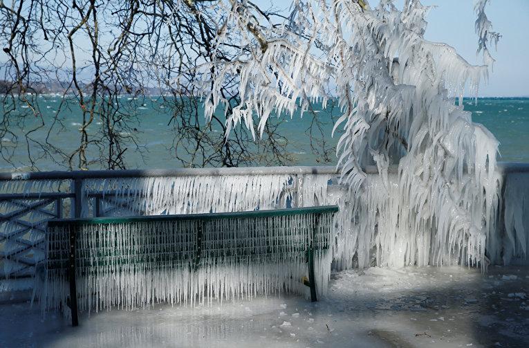 Фотография скамейки, покрытой льдом, снята на берегу замерзшего Женевского озера в Женеве, Швейцария.