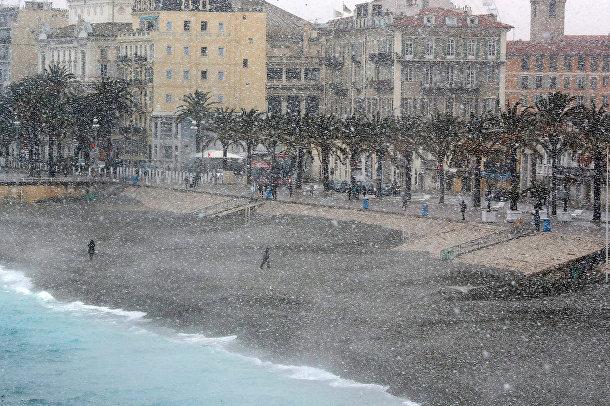 Люди идут под сильным снегопадом по Английской набережной в Ницце