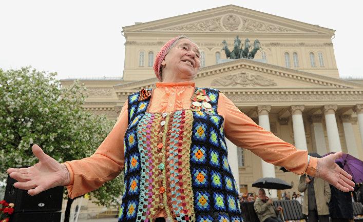 Пожилая женщина танцует во время встречи ветеранов в Москве