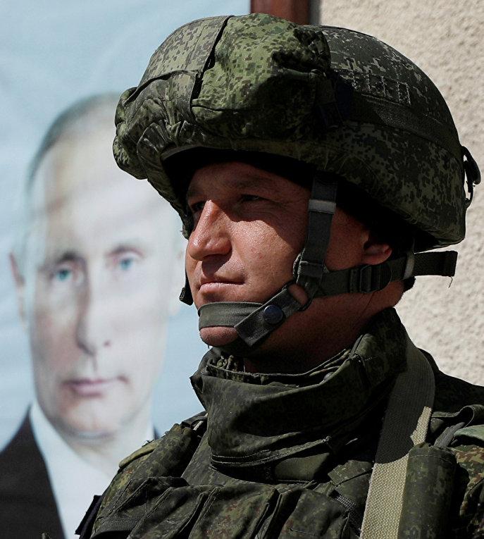 Российский солдат рядом с портретом президента России Владимира Путина в Дамаске