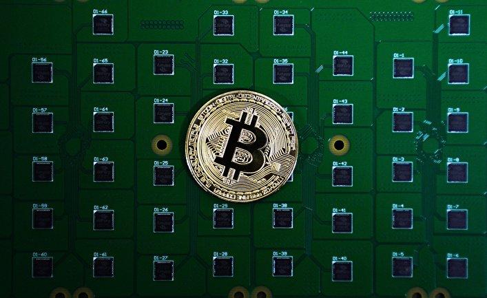 Сувенирная монета биткоина на фоне электрических плат