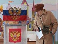 Пожилая женщина голосует на выборах президента РФ на избирательном участке в Санкт-Петербурге