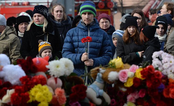 Жители несут цветы и мягкие игрушки к зданию торгового центра «Зимняя вишня» в Кемерово, где произошел пожар