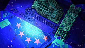 Рубли и евро: денежные купюры под ультрафиолетовым освещением