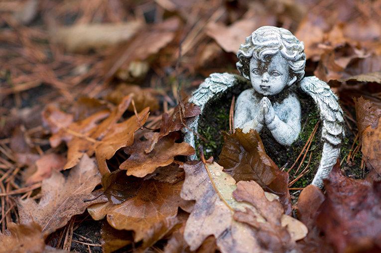 Фигурка молящегося ангела на кладбище