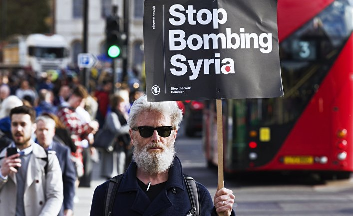 Мужчина держит плакат, призывающей не бомбить Сирию, на акции протеста против ударов по Сирии в Лондоне