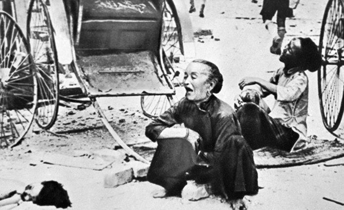 Убитая горем малазийка плачет над телом ребенка (справа) после японской бомбардировки 13 марта 1942 года во время одного из последних рейдов перед захватом Сингапура японцами.