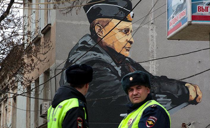 Сотрудники ДПС на фоне граффити с изображением президента России Владимира Путина в Симферополе