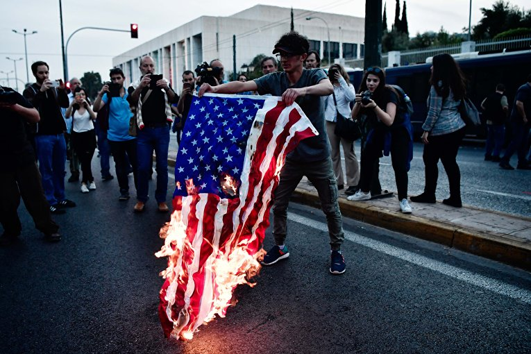 Сожжение флага США перед зданием посольства Сша в  Афинах в Греции. 14 апреля 2018