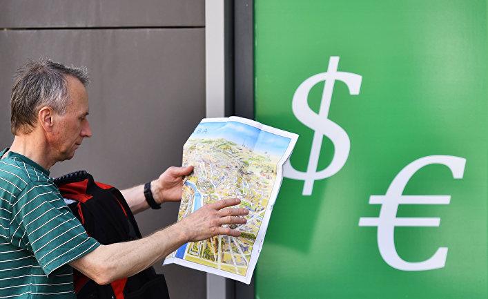 Мужчина у пункта обмена валюты на одной из улиц Москвы