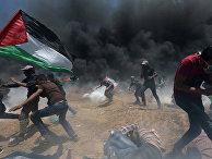 Палестинские демонстранты убегают от слезоточивого газа во время акции протеста против переноса посольства США в Иерусалим