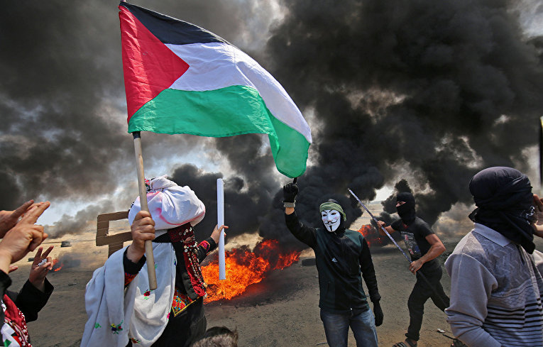 Палестинские демонстранты во время акции протеста против переноса посольства США в Иерусалим на границе Израиля и сектора Газа