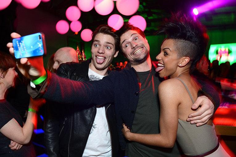 Гости на вечеринке в Лос-Анжелесе фотографируются на смартфон