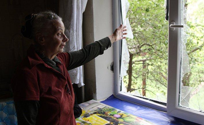 Жительница демонстрирует разбитое окно в жилом доме, пострадавшем в результате обстрела, в поселке Горловка Донецкой области. 21 мая 2018
