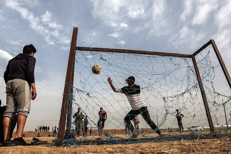 Палестинская молодежь играет в футбол у границы с Израилем