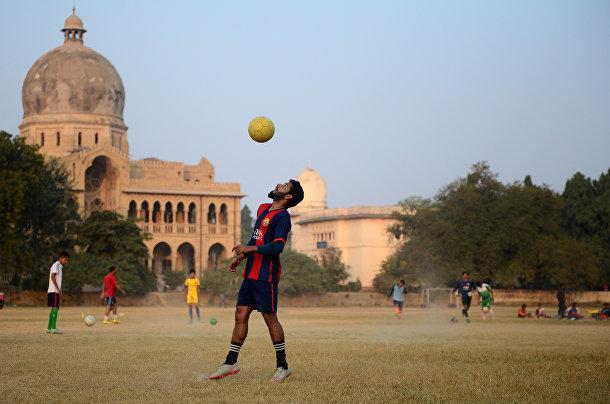 Мужчина играет в футбол в кампусе университета Аллахабад в Аллахабаде, Индия