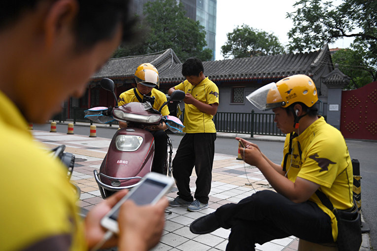 Курьеры службы доставки в ожидании заказов в Пекине