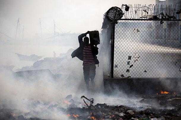 Мужчина несет контейнер с морской водой для тушения огня в гавани Порт-о-Пренса, Гаити