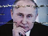 Разорванный плакат с изображением президента России Владимира Путина в Митровице, Сербия