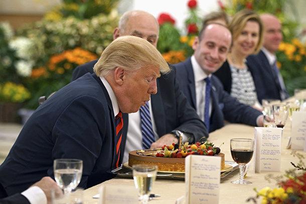 Президент США Дональд Трамп задувает свечи на торте