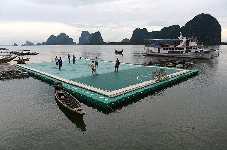 Дети играют на плавучей футбольной площадке в Таиланде