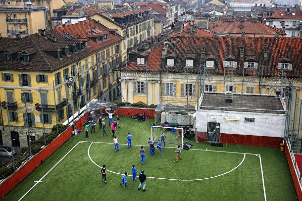 Школьники играют в футбол на крыше Колледжа в Турине