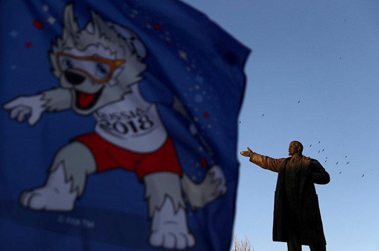 Флаг с официальным талисманом ЧМ-2018 рядом со статуей Ленина в Волгограде