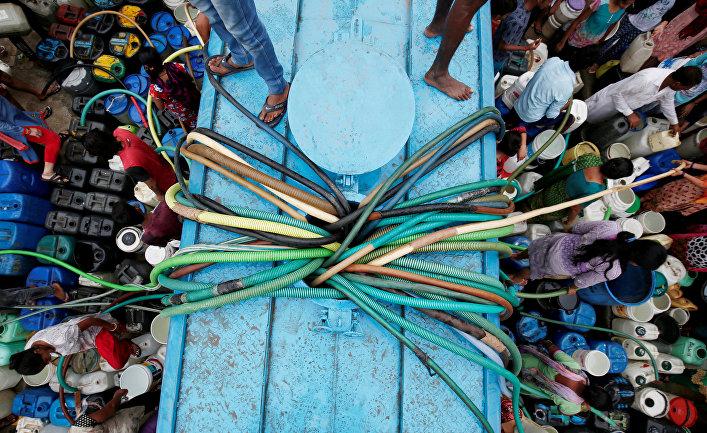 Жители пополняют запасы питьевой воды из муниципального танкера в Нью-Дели