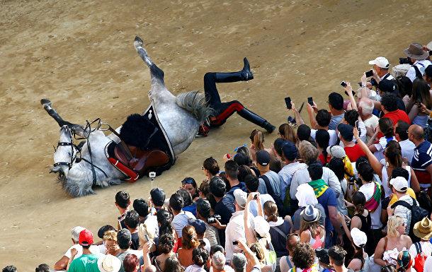 Итальянский полицейский падает с лошади во время парада перед скачками в Сиене