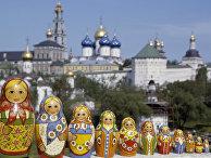 Русские матрешки, сфотографированные на фоне Троице-Сергиевой лавры
