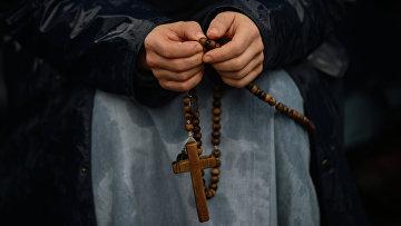 Католик молится, перебирая четки