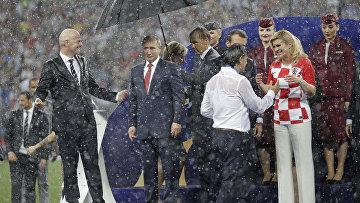 Президент ФИФА Джанни Инфантино обращается к президенту России Владимиру Путину, в то время как президент Хорватии Колинда Грабар-Китарович поздравляет тренера хорватской сборной Златко Далича после матча против Франции в финале ЧМ-2018