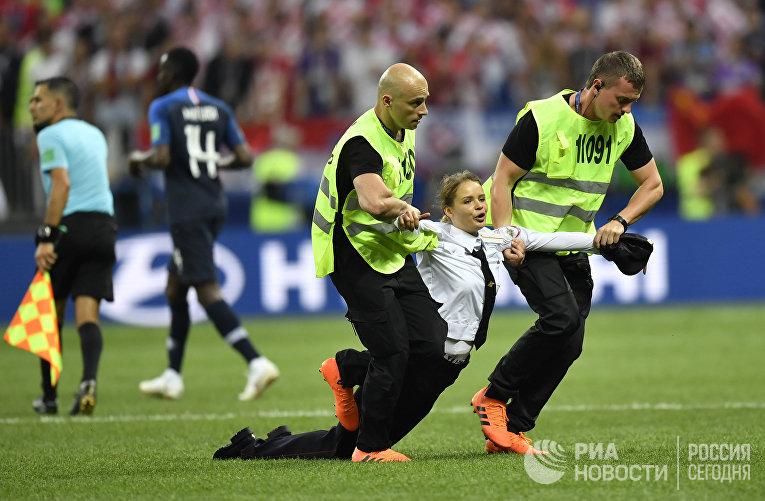 Охрана утаскивает участницу Pussy Riot, которая выбежала наполе вовремя матча Франция— Хорватия вфиналеЧМ пофутболу вМоскве