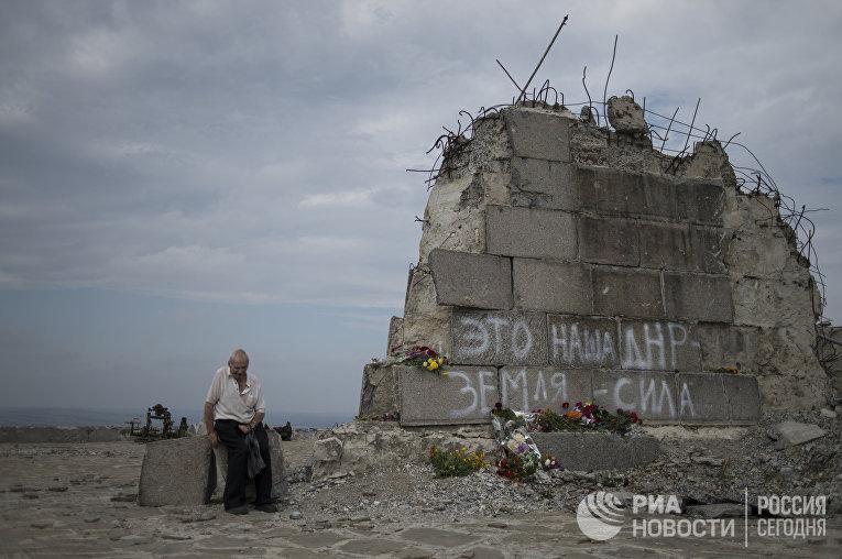 Мужчина у мемориала на кургане Саур-Могила в Донецкой области