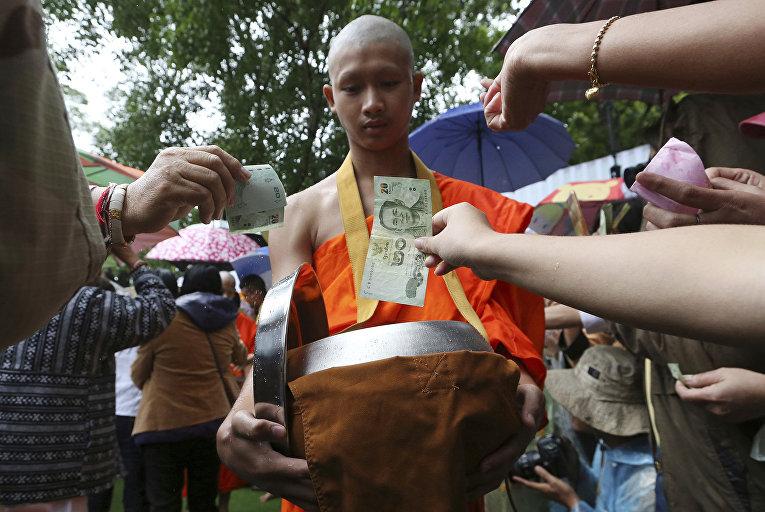 Буддийский монах собирает пожертвования для футбольной команды, спасенной из затопленной пещеры в Тайланде