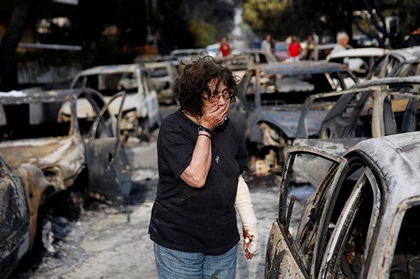 Женщина пытается найти свою собаку после разрушительного пожара в Греции