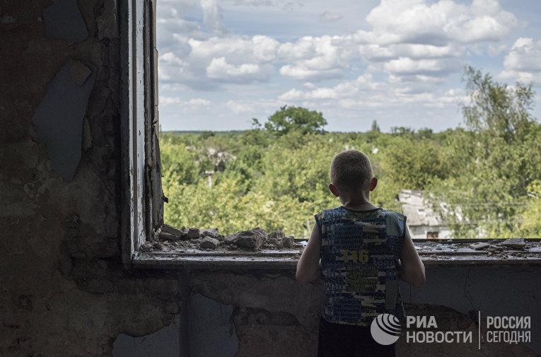 Подросток у окна в разрушенном спортивном зале средней школы поселка Шахты 6/7 близ Горловки