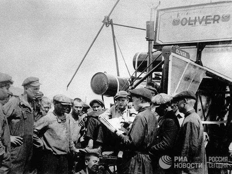 Рабочие совхоза изучают инструкцию по эксплуатации комбайна