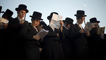 Ультраортодоксальные евреи молятся на берегу реки Хаяркон