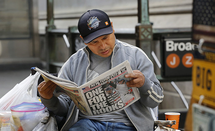 Мужчина читает газету в Нью-Йорке