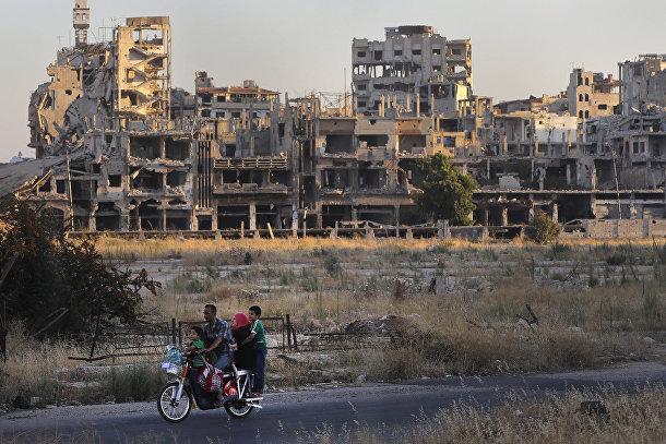 Люди едут на мотоцикле мимо поврежденных зданий в городе Хомс, Сирия