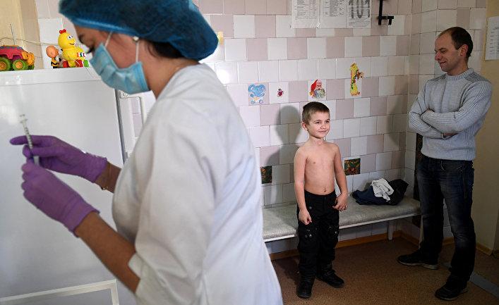 Медсестра готовит шприц для вакцинации против кори в детской поликлинике в Киеве