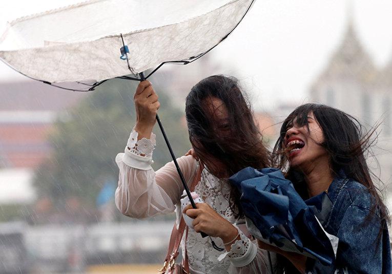 Прохожие во время сильного дождя в Бангкоке, Таиланд