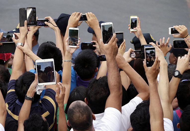 Филиппинские католики готовятся сделать фотографии во время визита Папы Франциска в Манилу