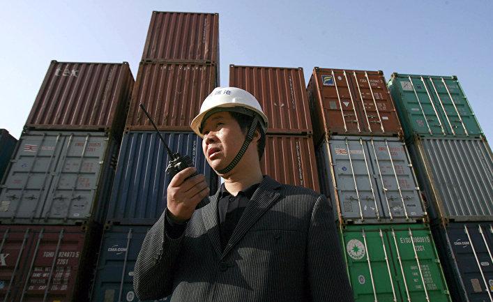 Рабочий следит за погрузкой контейнеров в порту в Ухане, Китай