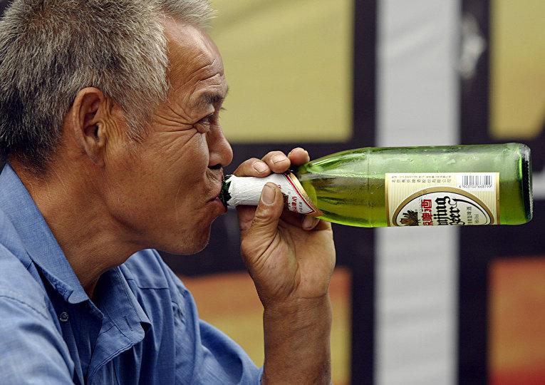 Мужчина пьет пиво в Пекине, Китай