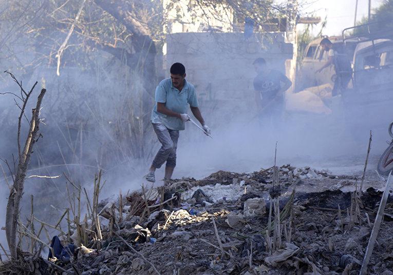 Местные жители тушат пожар на месте авиаудара в сирийской провинции Идлиб