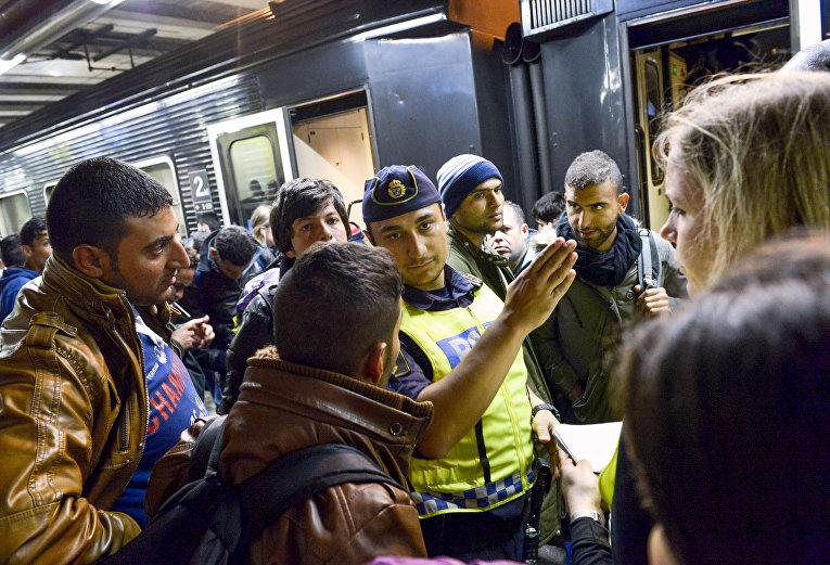 Сотрудник шведской полиции на вокзале в Стокгольме показывает дорогу мигрантам, прибывшим из Мальме