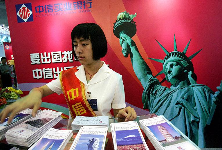 Девушка у стенда китайской компании CITIC на Международной выставке финансовой культуры в Пекине, КНР