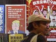 Плакат с изображением президента США Дональда Трампа и сообщением о введении 25% торговых пошлин на товары из Китая в Гуанчжоу